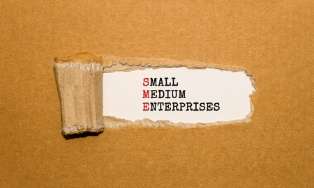 Photo for The text SME SMALL MEDIUM ENTERPRISES appearing behind torn brown paper - Royalty Free Image