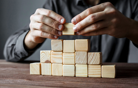Photo for Businessman building a pyramid with empty wooden cubes. Concept of business hierarchy and business strategy. - Royalty Free Image