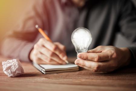 Foto de Businessman holding light bulb and writing down in the notebook new creative ideas. Concept of innovative technology and creativity. - Imagen libre de derechos