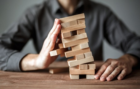 Foto de Businessman holds the model of business, made from wood blocks. Alternative risk concept, business plan and business strategy. Insurance concept. - Imagen libre de derechos