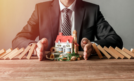 Photo pour Close-up of a man stopping the wooden blocks from falling on house model. House insurance and security concept. - image libre de droit