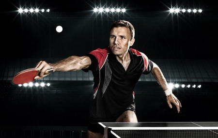 Portrait Of Young Man Playing Tennis On Black Background with lights