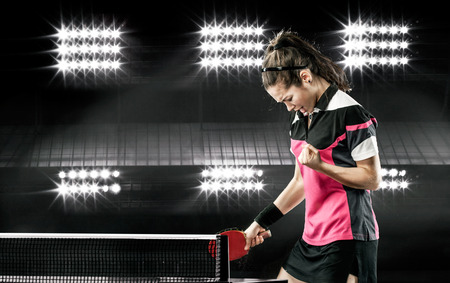 Portrait Of Young Girl Celebrating Flawless Victory in Table Tennis On Dark Background with lights