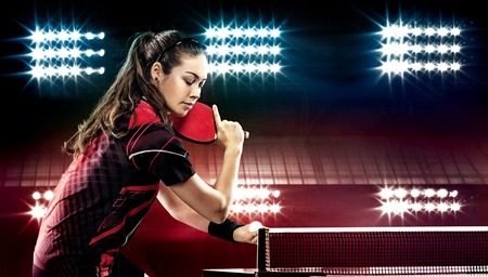 Portrait Of Young Woman Playing Tennis On Black Background with lights