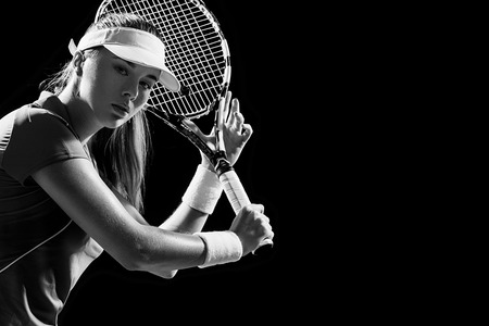 Portrait of beautiful girl tennis player with a racket isolated on black background