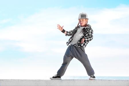 Foto de Happy little girl dancing hip-hop on blue sky background - Imagen libre de derechos