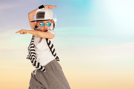 Foto de Happy little girl dance on sky background. Fashion kid. Copy space. - Imagen libre de derechos