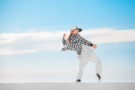 Photo for Fashion child dancing over sky background. - Royalty Free Image