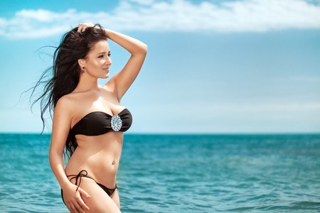 Photo pour Overweight young woman in black swimsuit near the sea. Size plus or king size woman. Summer photo with copy space - image libre de droit