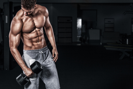 Photo pour Athletic shirtless young sports man - fitness model holds the dumbbell in gym. Copy space fore your text. - image libre de droit