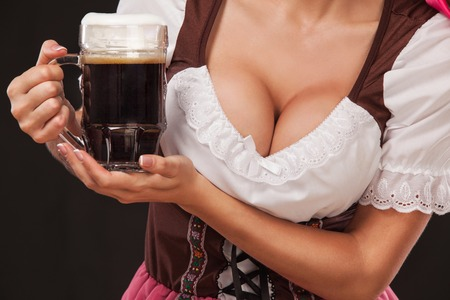 Foto de Closeup portrait of boyd Oktoberfest girl - waitress, wearing a traditional Bavarian dress, serving big beer mugs on black background. - Imagen libre de derechos