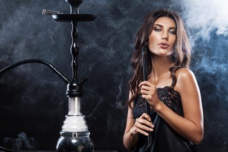Photo pour Young, beautiful woman in the night club or bar smoke a hookah or shisha. The pleasure of smoking. Sexy smoke. - image libre de droit