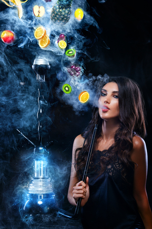 Photo for Young, beautiful woman in the night club, bar smoke a hookah or shisha. The pleasure of smoking. Fruits in the smoke. Copy space. Hookah advertisement concept. - Royalty Free Image