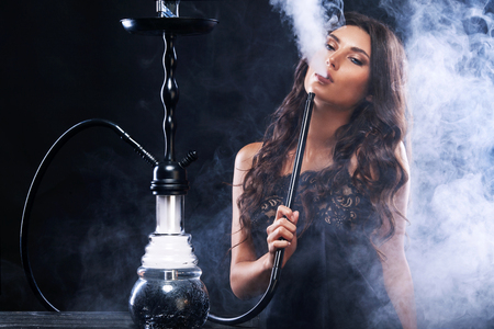 Photo for Young, beautiful woman in the night club or bar smoke a hookah or shisha. The pleasure of smoking. Sexy smoke. - Royalty Free Image