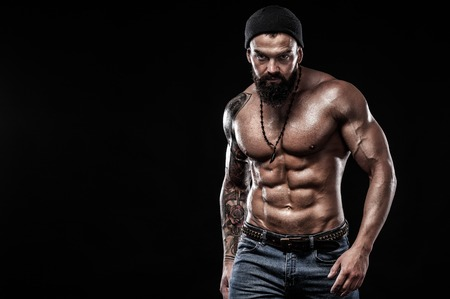 Photo pour Handsome fit man posing wearing in jeans with tattoo. Sport and fashion concept isolated on black background. - image libre de droit
