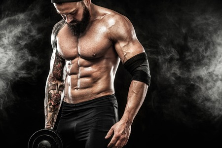 Photo pour Muscular young fitness sports man workout with dumbbell in fitness gym - image libre de droit