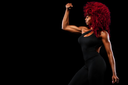 Photo pour A strong athletic woman on black background wearing in sportswear, fitness and sport motivation. Sport concept with copy space. - image libre de droit