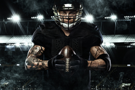 Photo for Sport concept. American football sportsman player holding ball on stadium. - Royalty Free Image