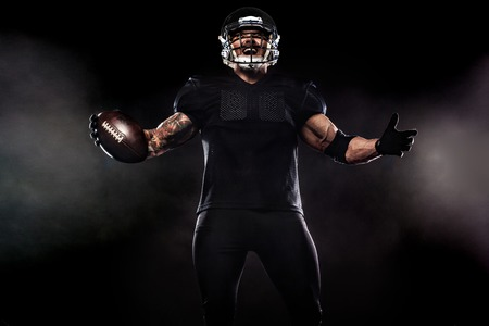Photo pour American football sportsman player isolated on black background - image libre de droit
