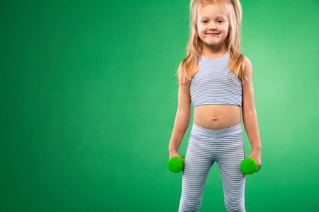 Photo for Kid doing fitness exercises at home in her room - Royalty Free Image