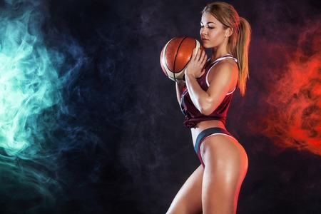 Photo pour Beautiful and sexy fit woman with a basketball in studio. Sport concept - image libre de droit