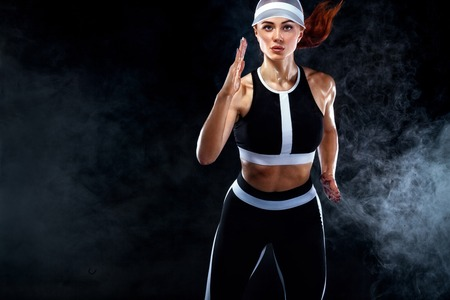 Photo for Strong athletic woman sprinter, running on black background wearing in the sportswear. Fitness and sport motivation. Runner concept with copy space. - Royalty Free Image