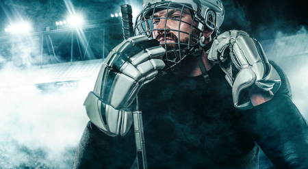 Foto per Ice Hockey player in the helmet and gloves on stadium with stick. - Immagine Royalty Free