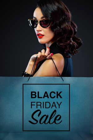 Photo pour Closeup portrait of black friday sale concept for shop. Woman in sunglasses holding big bag isolated on dark background at shopping. - image libre de droit