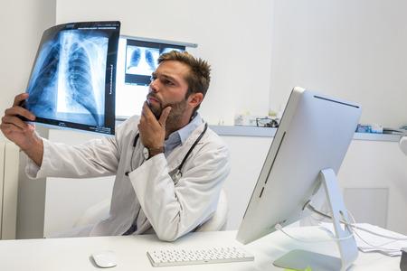 Photo pour Serious attractive doctor examining an x-ray - image libre de droit