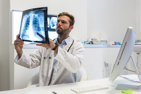 Photo pour Serious attractive doctor examining an x-ray - image libre de droit