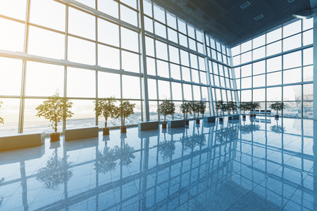 Photo pour Interior of the modern lobby, terminal or waiting room with glass walls and reflective floor,  natural light and flare - image libre de droit