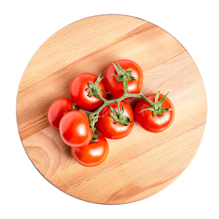 Photo for Fresh Red ripe tomatoes on a green branch laying on wooden beech board. Isolated on white background - Royalty Free Image