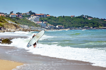 Photo pour Surfer walks on sandy beach with surfboard. Atlantic ocean coast. Wave - image libre de droit