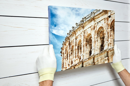 Foto de Photography printed on canvas with gallery wrap method of canvas stretching in male hands. Image of architecture of Nimes city, France - Imagen libre de derechos