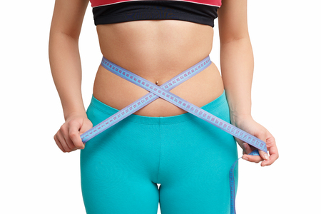 Foto per fitness girl measuring waist by a centimeter on a white background - Immagine Royalty Free