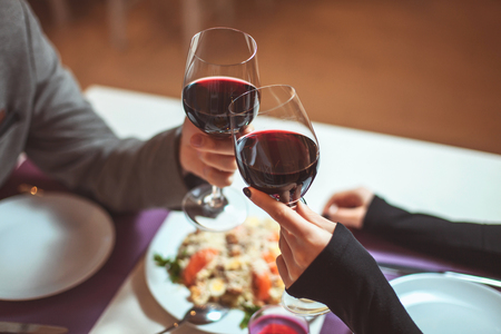 Photo for Beautiful young couple with glasses of red wine in luxury restaurant - Royalty Free Image