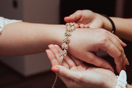 Foto de Bridal preparation, bride putting on jewelry, focus on bracelet - Imagen libre de derechos