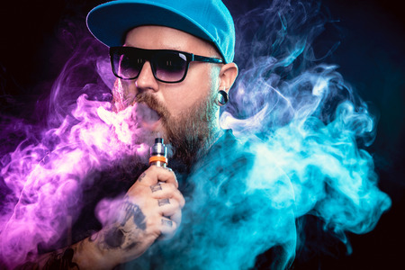 Foto de Men with beard  in sunglasses vaping and releases a cloud of vapor. - Imagen libre de derechos