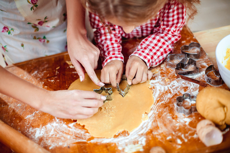 Foto de Merry Christmas and Happy Holidays. Family preparation holiday food. Mother and daughter cooking cookies in New Year interior with Christmas tree. - Imagen libre de derechos