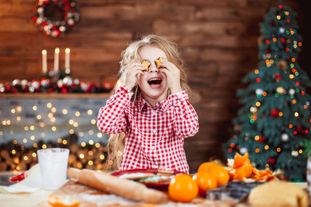Foto de Happy little child, cute kid girl at the table in domestic kitchen making gingerbread xmas cookies decorated for Christmas holiday. Girl helping and having fun - Imagen libre de derechos