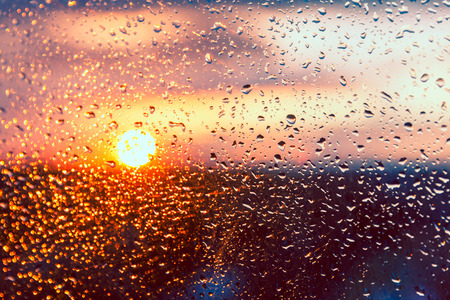Water drops on a window glass after the rain. The sky with clouds and sun on background.