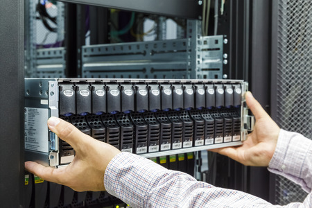 Foto de IT Engineer installs equipment in the rack in datacenter - Imagen libre de derechos