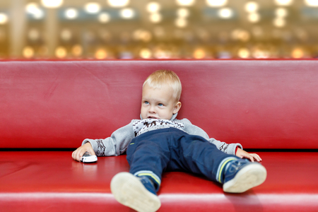 Photo for Child is lying on the couch in the shopping center or mall. Little boy tired during shopping with parents. - Royalty Free Image
