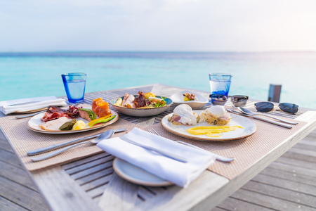 Photo for Luxury breakfast food on wooden table, with beautiful tropical Maldives island background, morning time holiday vacation concept. - Royalty Free Image
