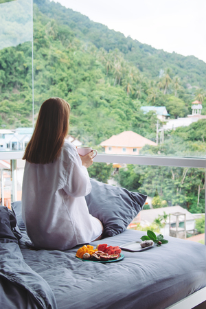 Photo pour causacian girl waking up white mans shirt grey bed linens mountant coffee fruit - image libre de droit