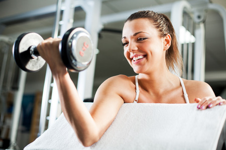 Cute Sporty young woman doing exercise in a fitness center. She is working exercises to strengthen her biceps.