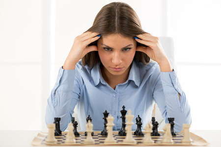 Foto für A young businesswoman is sitting in front of a chess board and thinking staring at the figure, holding hands on her head. - Lizenzfreies Bild