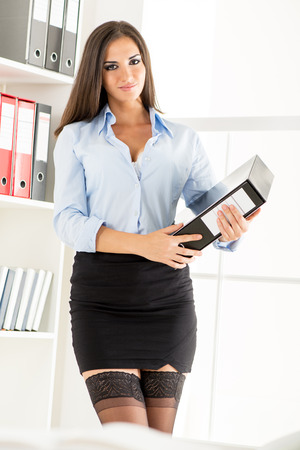 Photo pour Young pretty businesswoman in a short skirt, holding a binder and smiling looking at the camera. - image libre de droit