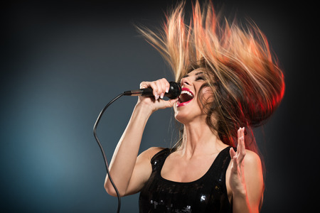 Photo pour A young woman rock singer with tousled long hair holding a microphone with stand and sing with a wide open mouth. - image libre de droit