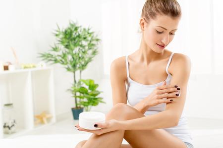 Foto de Beautiful young woman applying body lotion. - Imagen libre de derechos